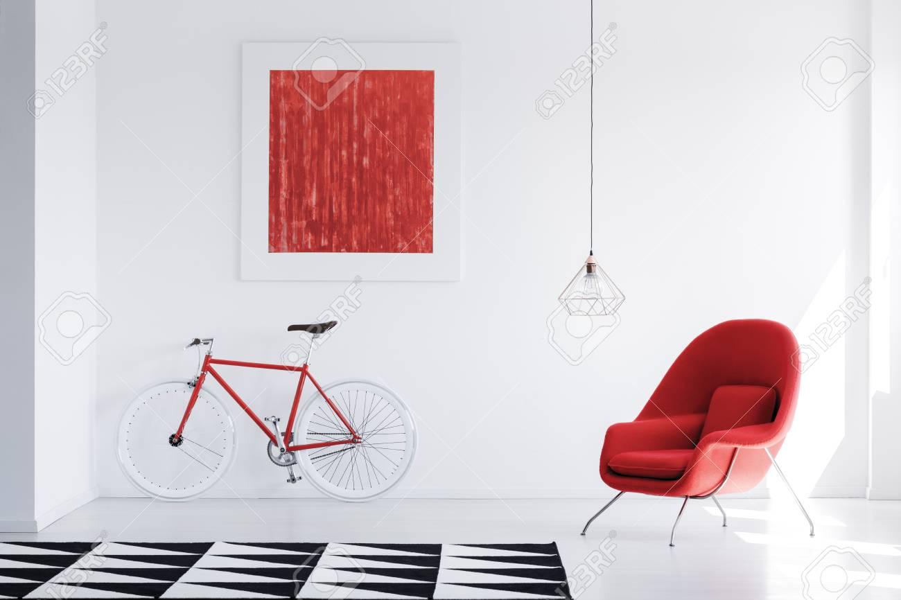 Lampe Au Dessus Du Fauteuil Rouge Dans Un Intérieur Lumineux Avec Tapis Noir Et Blanc Et Peinture Rouge Sur Le Mur Au Dessus Du Vélo