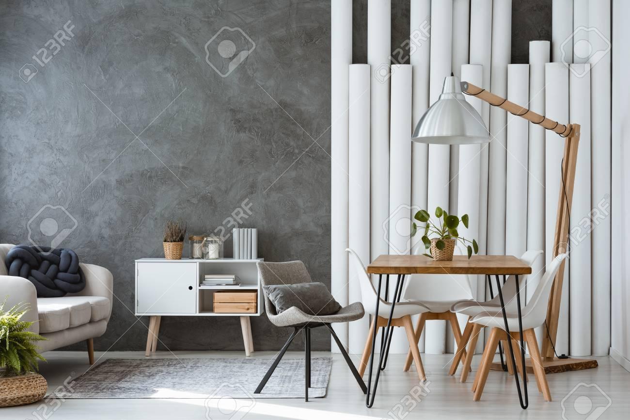Lámpara de diseño encima de la mesa de comedor en la sala de estar  monocromática con tubos de papel, sofá y armario