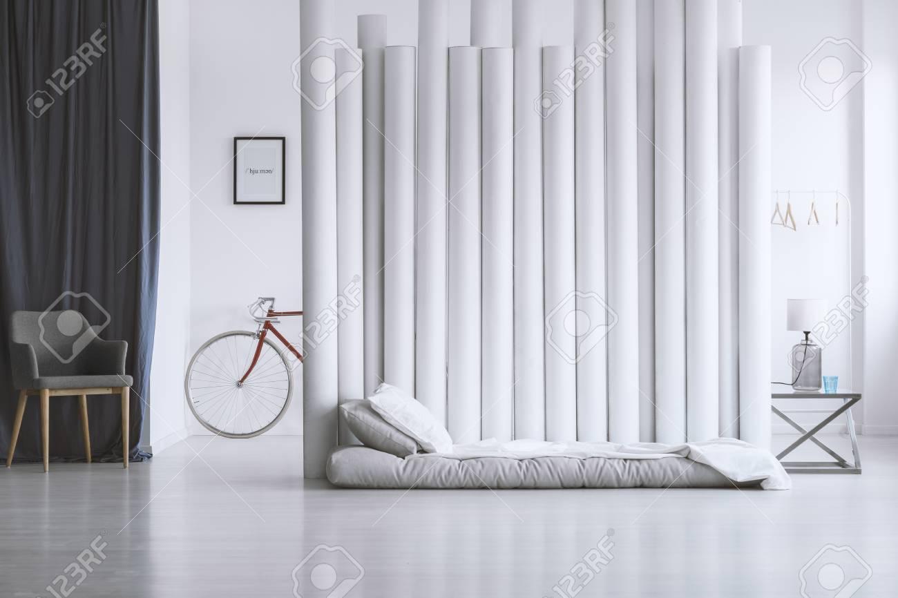 Chambre Matelas Au Sol matelas gris sur le sol contre l'écran de concepteur dans la chambre à  coucher spacieuse avec chaise grise contre le rideau foncé