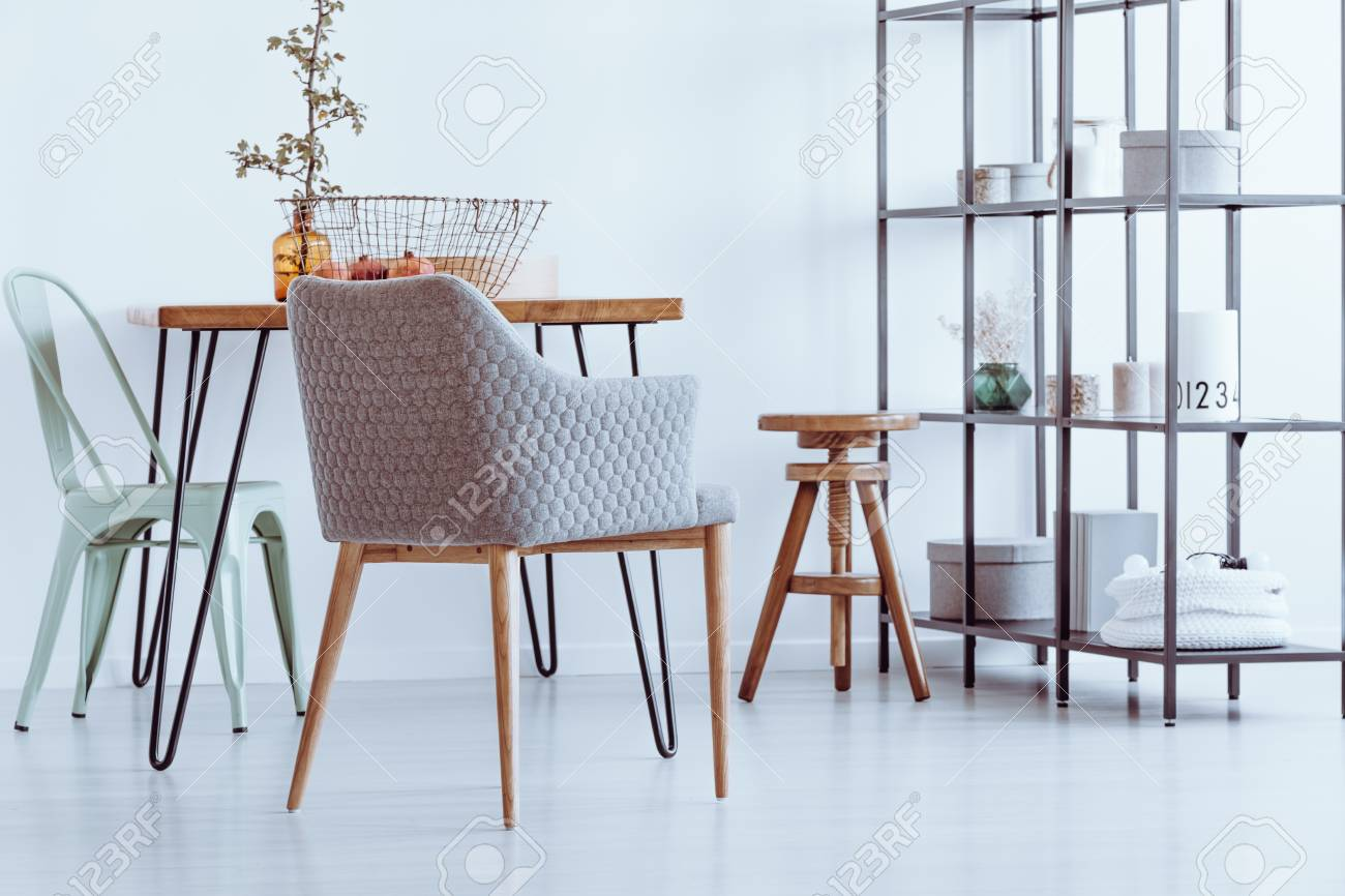 Grey Armchair, Wooden Stool And Mint Chair Standing By A Hairpin Table In  Bright,