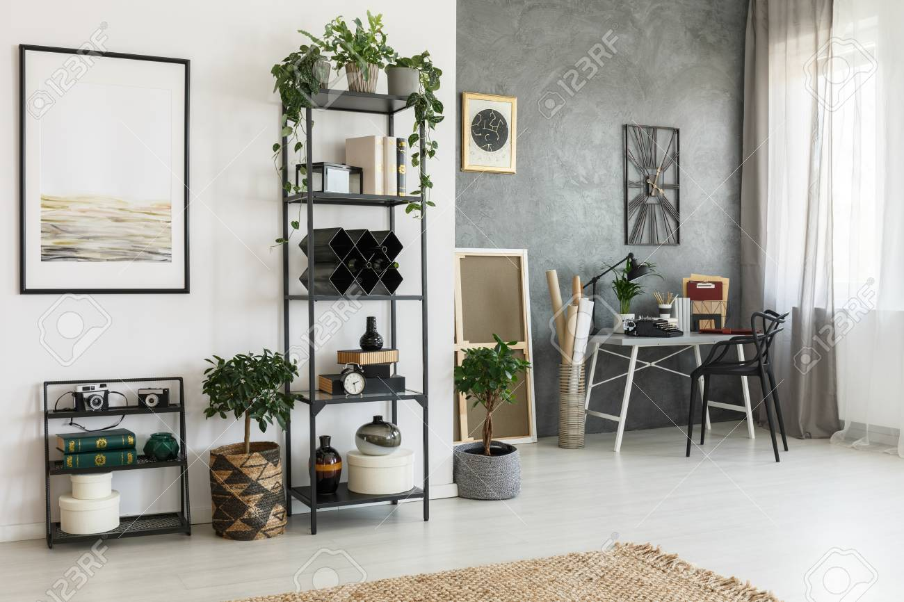 photo simple painting on white wall in living room with decorations on a shelf and plants on the floor