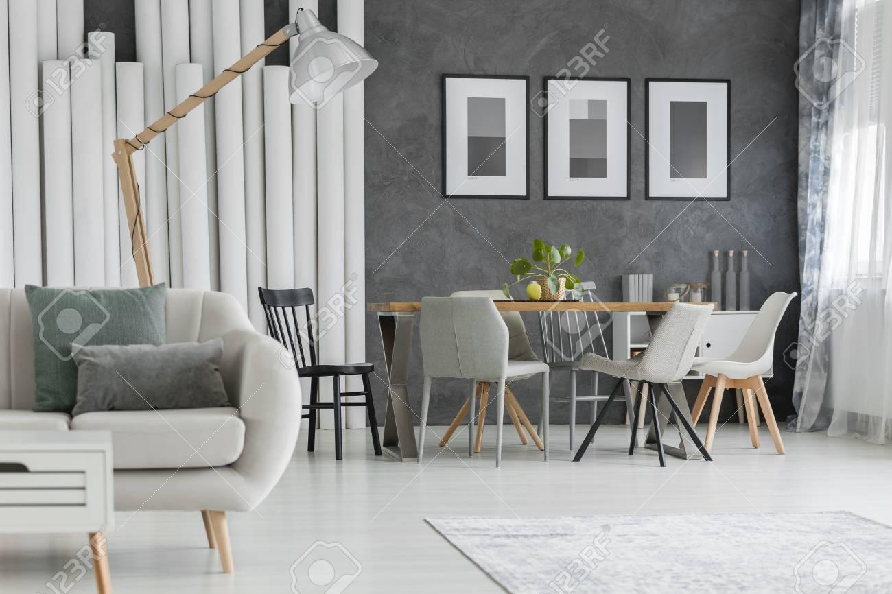 Beige Sofa Mit Kissen Und Designerlampe Im Esszimmer Mit Plakaten ...
