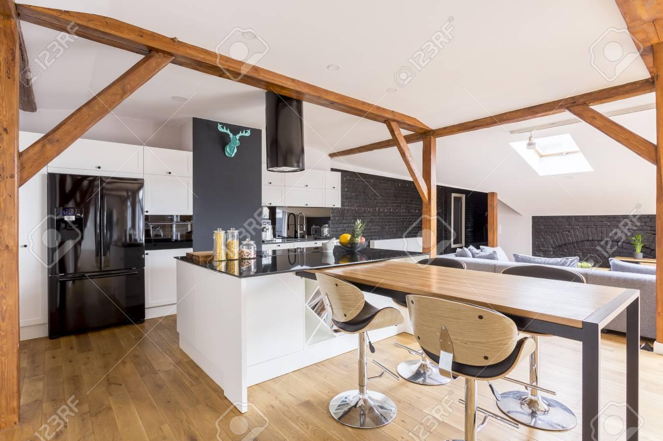 Isla de cocina clásica y mesa con taburetes en la cocina diseñada con  decoración azul en la pared negra