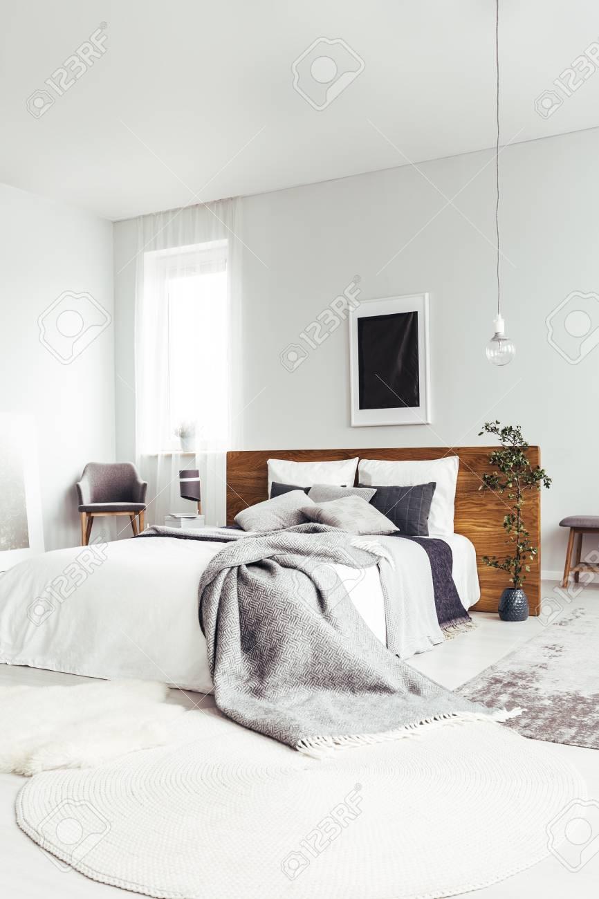 weißer teppich und kingsize-bett mit grauen bettwäsche im geräumigen hellen  schlafzimmer mit dunklem plakat