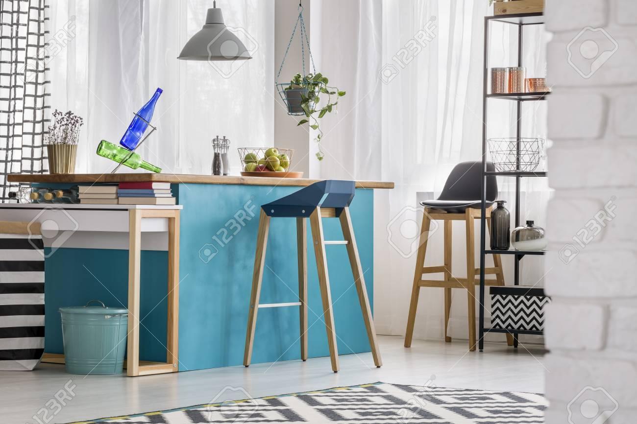 Hölzerner Barhocker Am Blauen Tisch Unter Grauer Lampe Im Modernen
