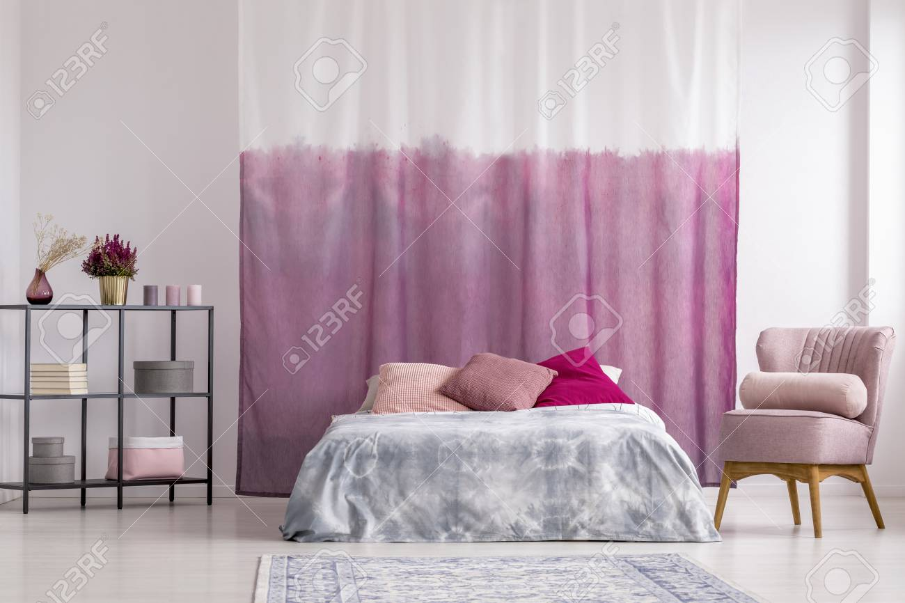 Pink armchair next to king-size bed with patterned pillows against..