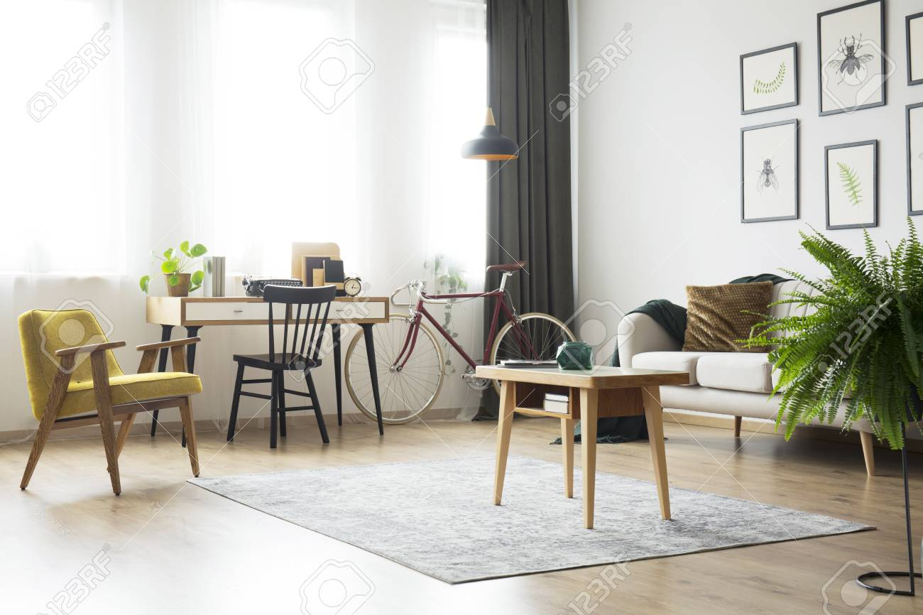 Stock Photo   Wooden Table On Carpet And Fern In Living Room With Home  Office With Retro Armchair And Bike