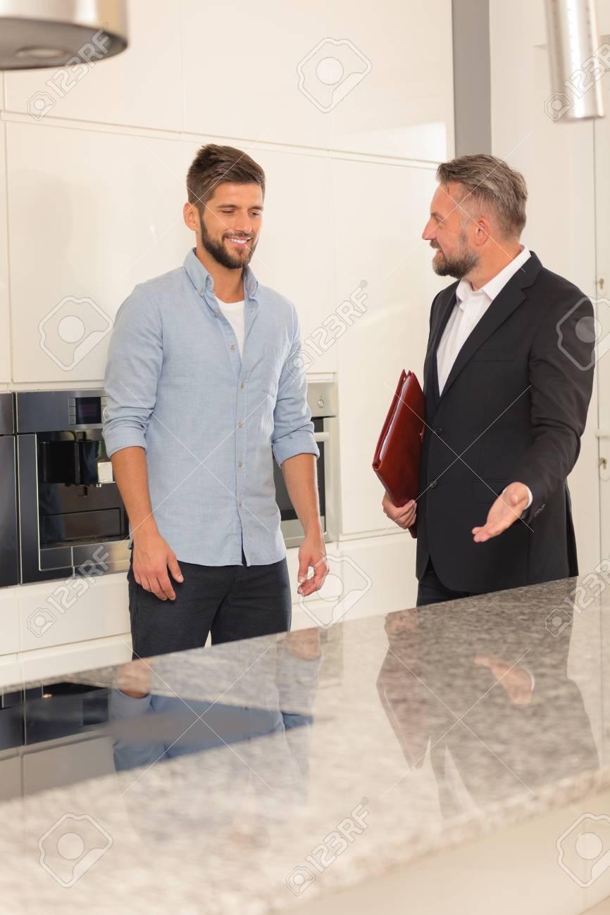 Agent Immobilier Et Acheteur Potentiel Debout Dans La Cuisine ...