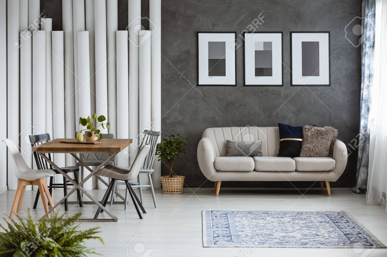 Multifunctional Monochromatic Living Room With Carpet Dining Table And Sofa Against Dark Wall Posters