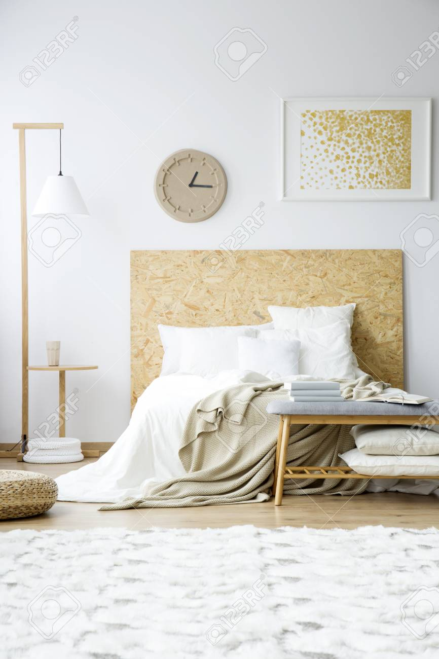 Paper Clock And Painting On The Wall Above Bed Next To A Wooden