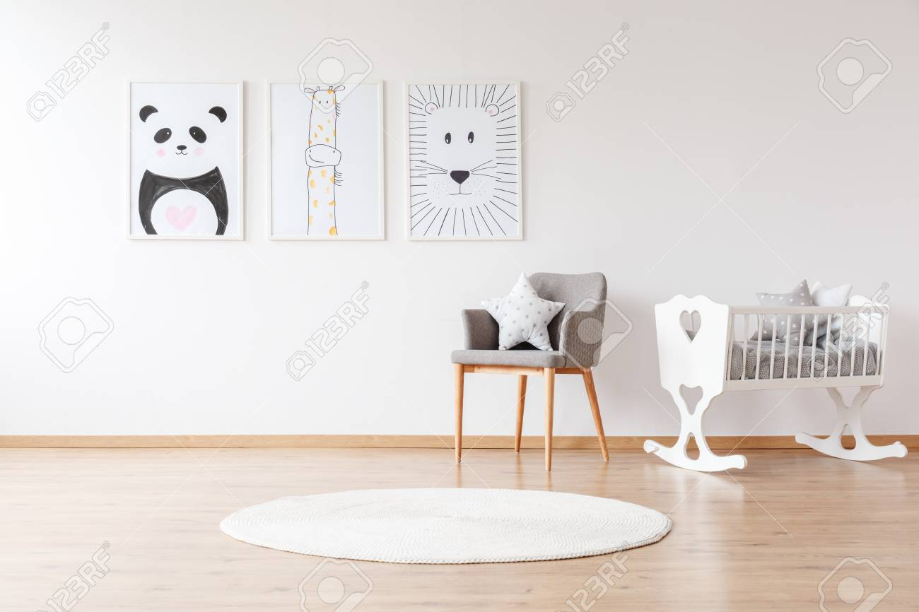 Grey chair with pillow and white round rug near white crib in baby's room with animal posters on the wall - 97990551