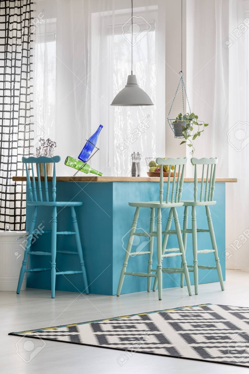 Colored Bar Stools At Blue Table In Bright Dining Room With