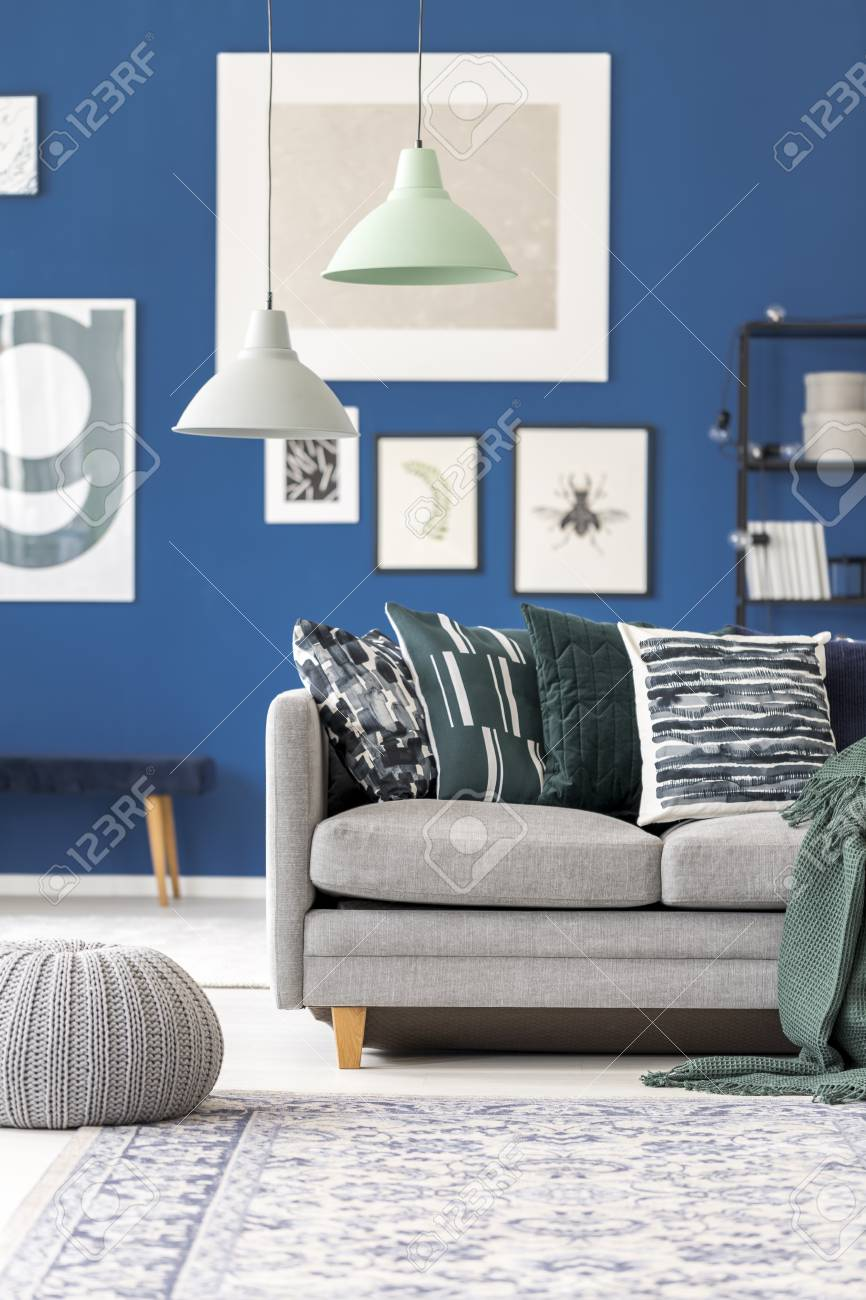 Pastel Lamps Above Grey Couch With Pillows Against Blue Wall Stock Photo Picture And Royalty Free Image Image 91939082