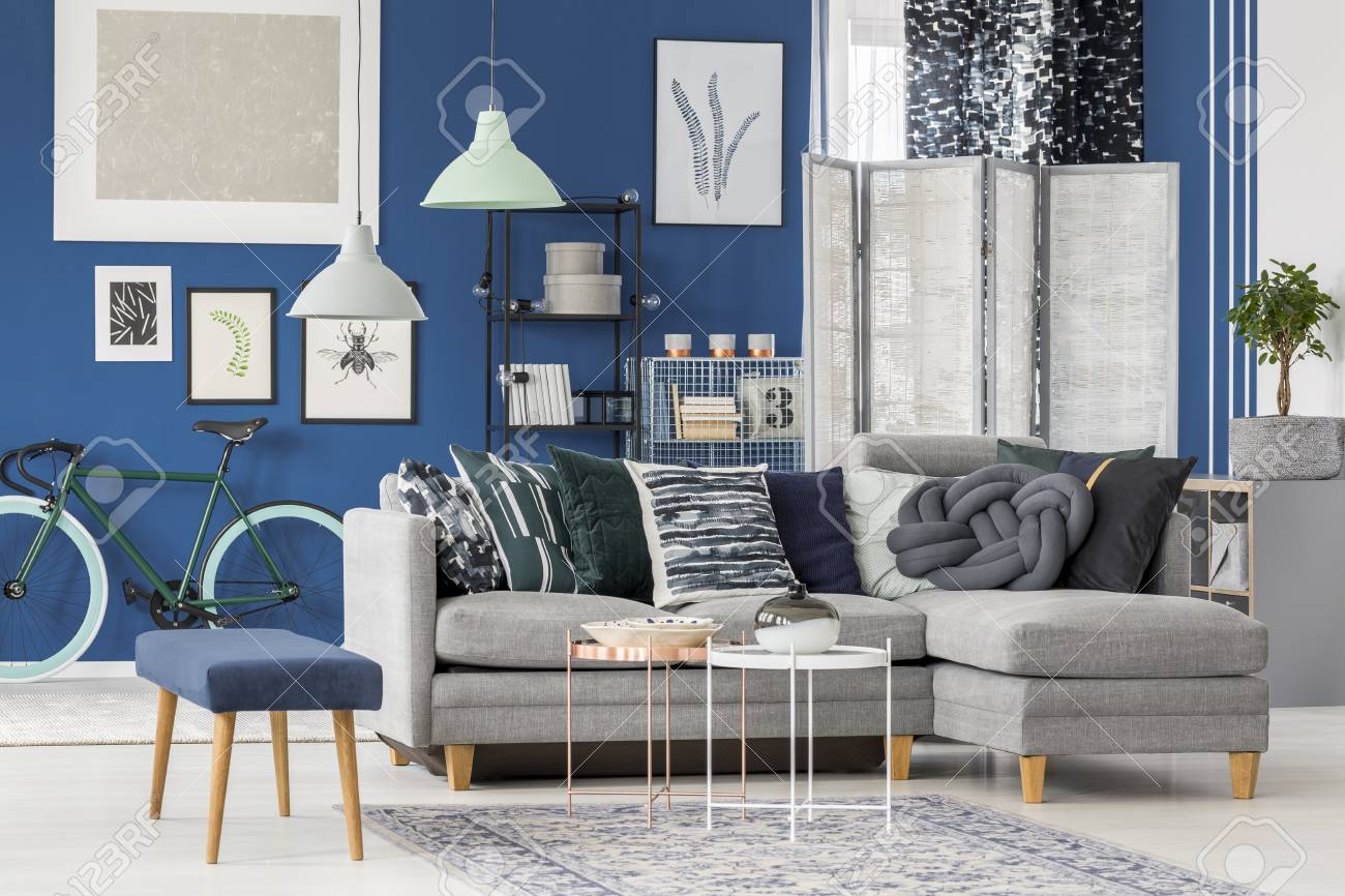 Blue stool near grey corner sofa with patterned pillows in living..