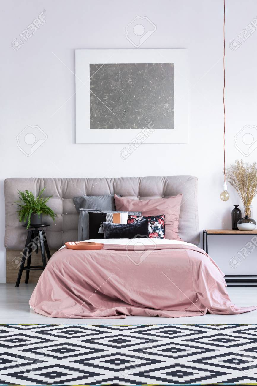 Tapis noir et blanc dans une chambre élégante avec literie rose foncé et  branche de fougère branche