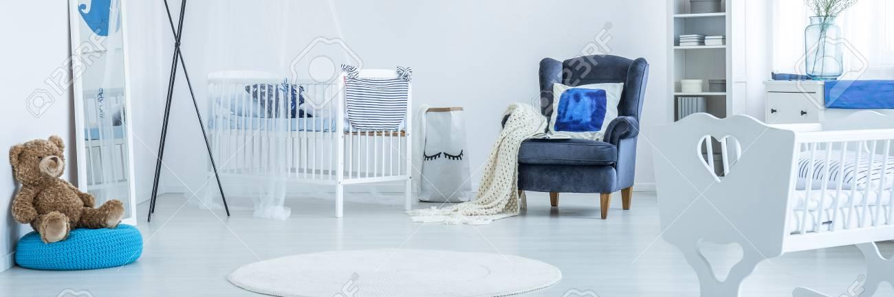 Lit bébé à l\'intérieur d\'une chambre d\'enfant spacieuse avec un fauteuil  bleu marine et un miroir