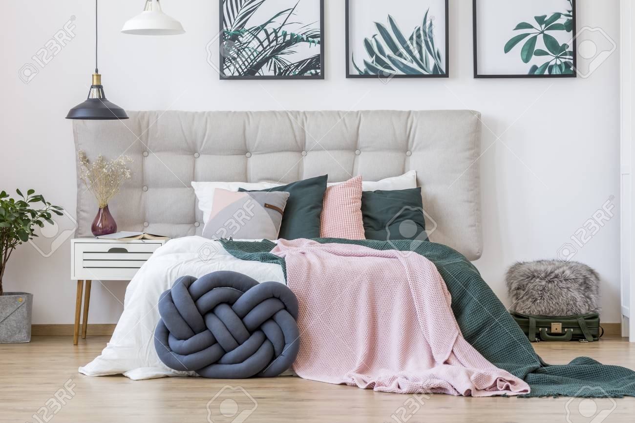 Knot pillow and green and pink bedding on bed in cozy bedroom..