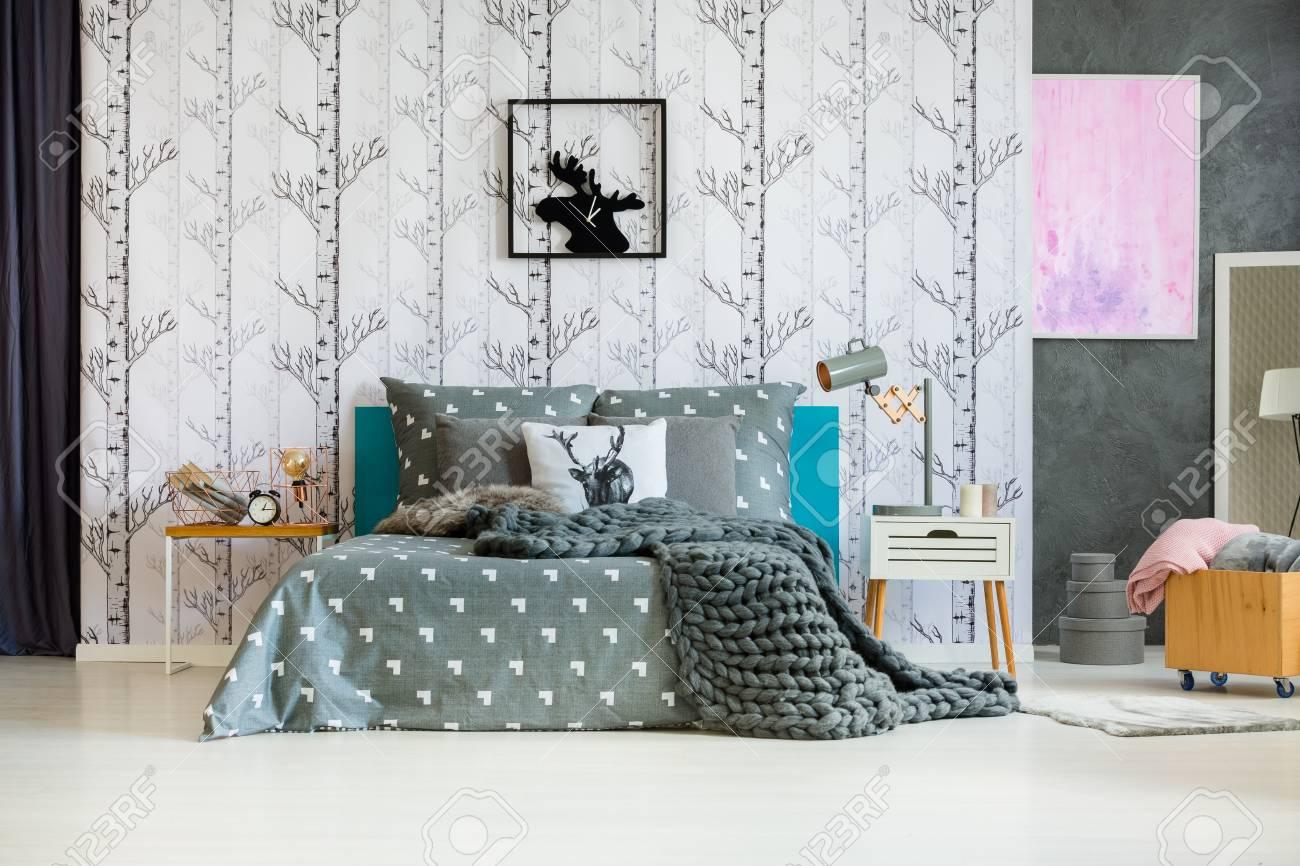 Tricoter une couverture grise sur un lit king-size dans la chambre à  coucher avec peinture rose et horloge d\'orignal sur fond d\'écran de la forêt