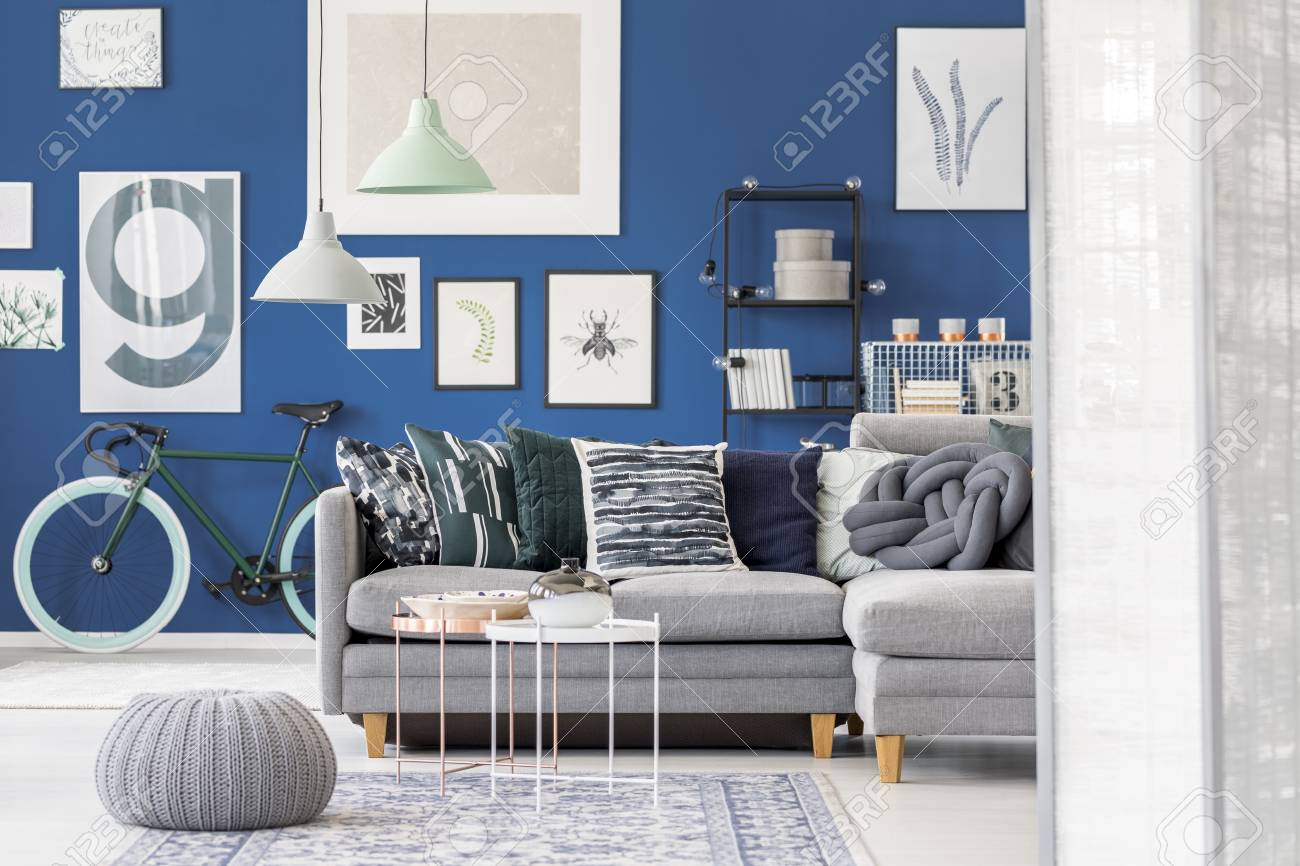 Grey pouf and tables on carpet in front of grey corner sofa with..