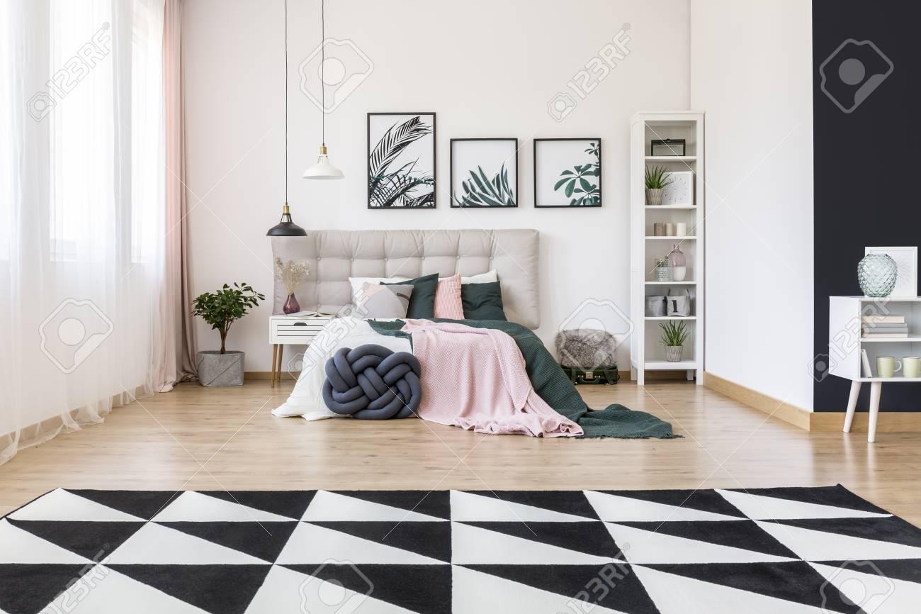 Tapis noir et blanc et plante dans une chambre intérieure spacieuse avec  des feuilles de lys rose et vertes sur le lit avec le siège beige