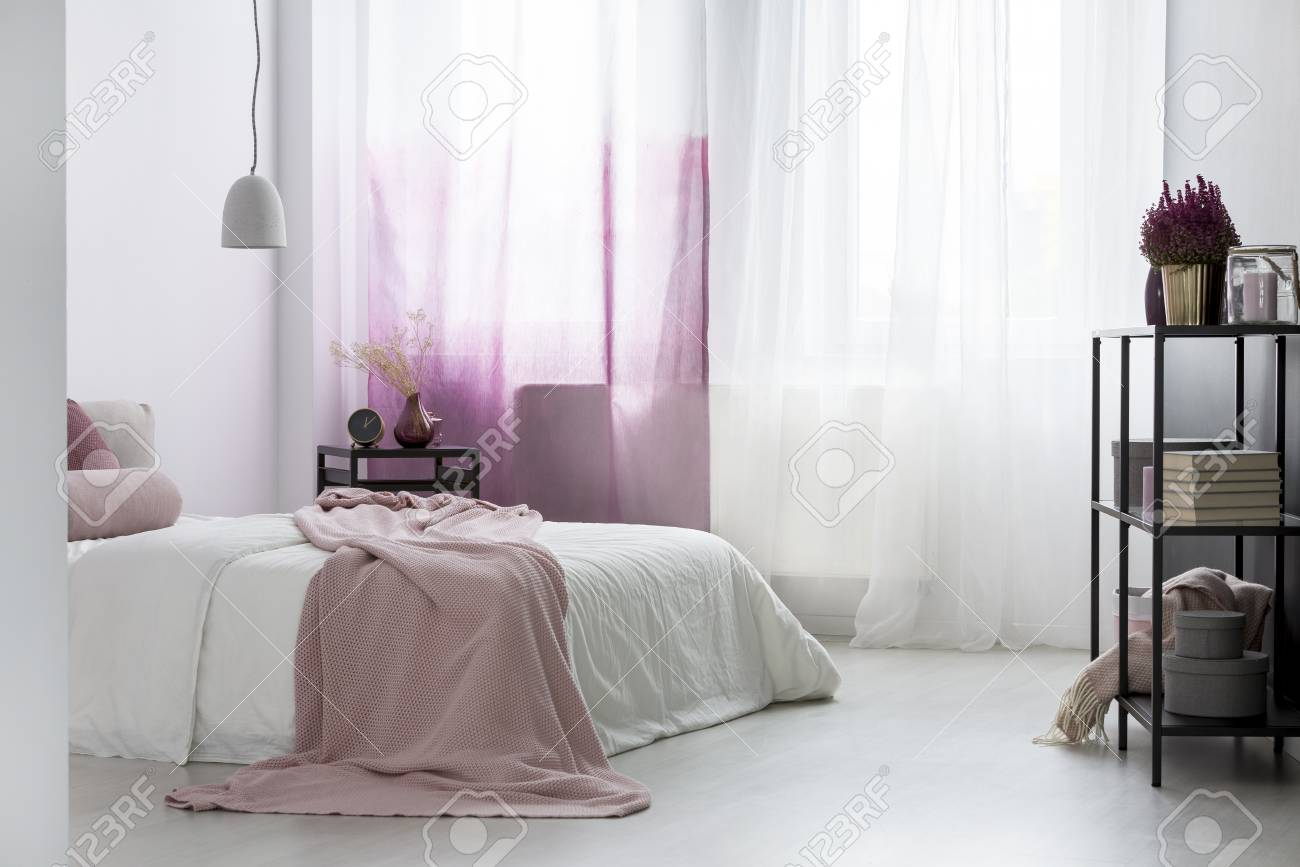 Pink blanket on bed and plant in gold pot on a shelf in bright..