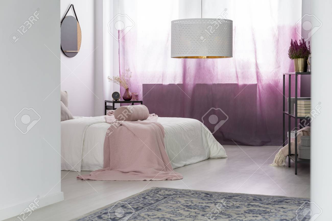 Stock photo white lamp above grey carpet in bedroom with pink curtains and mirror above bed with blanket