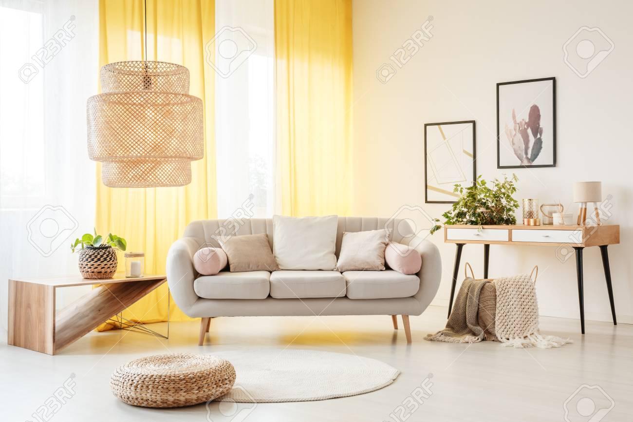 Lampe En Rotin Au Dessus Du Pouf Et Du Tapis Dans Le Salon Boheme Avec Canape Plantes Et Rideaux Jaunes