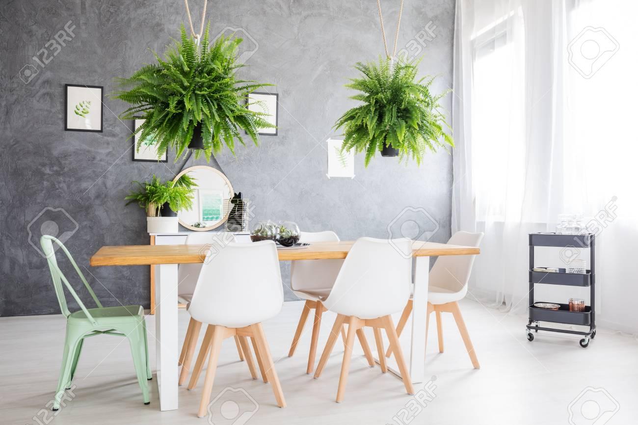 Miroir Salle De Sejour miroir reflétant une peinture verte, suspendu dans une salle de séjour  meublée d'une table à manger et de chaises confortables