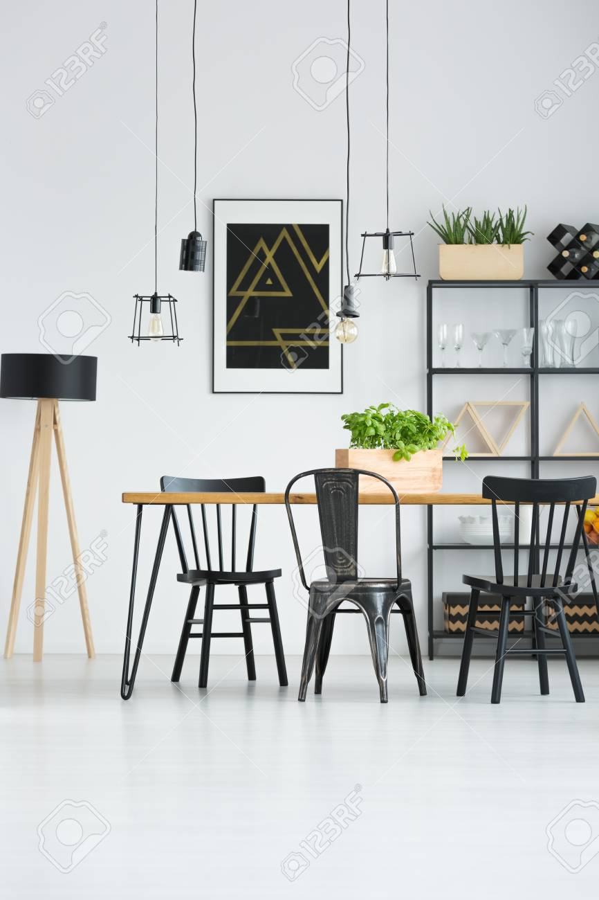 Lamps Above Dining Table With Black Chairs In Bright Interior Stock Photo Picture And Royalty Free Image Image 97990588