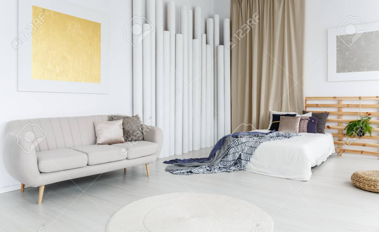 Bright Grey Couch With A Furry Pillow In Bedroom With Two Paintings And  Pillars Stock Photo