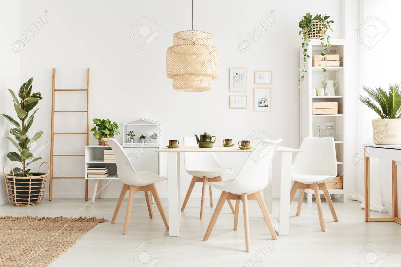 Big Wicker Lampshade Hanging Above Table In White Dining Room