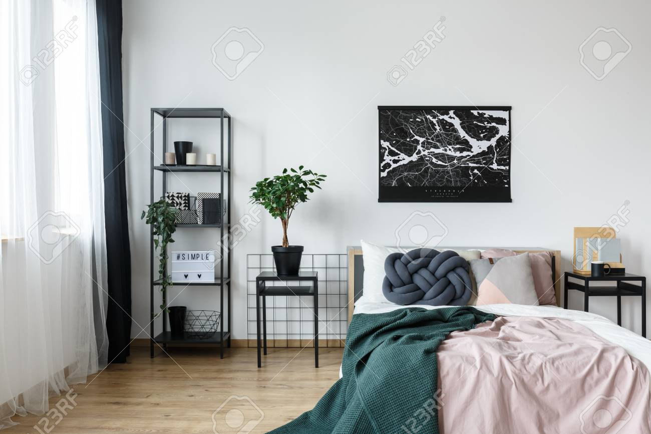 Black and white map poster hanging over pastel pink bed with..