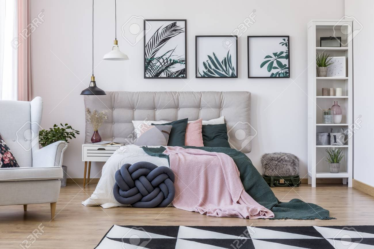 photo suitcase and grey armchair in cozy bedroom interior with knot pillow and pink blanket on bed