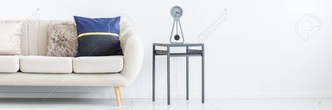 Beau Dekoratives Kissen Auf Beige Sofa Neben Hocker Mit Uhr Im Wohnzimmer Mit  Kopienraum Auf Der Wand