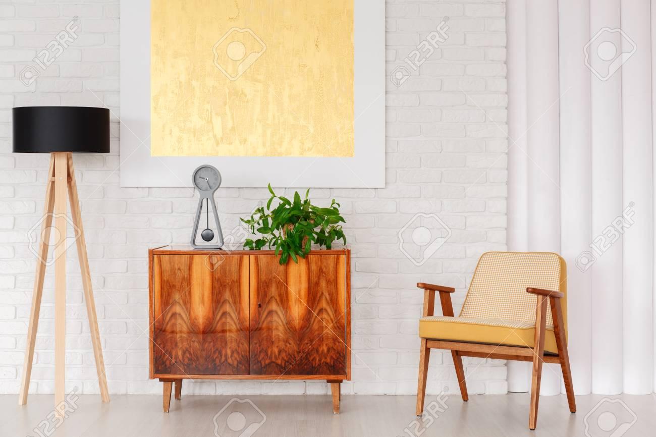 Chaise Vintage à Côté D Un Placard En Bois Avec Horloge Et Plante Contre Un Mur Avec Peinture Dorée Dans Le Salon Intérieur Avec Lampe