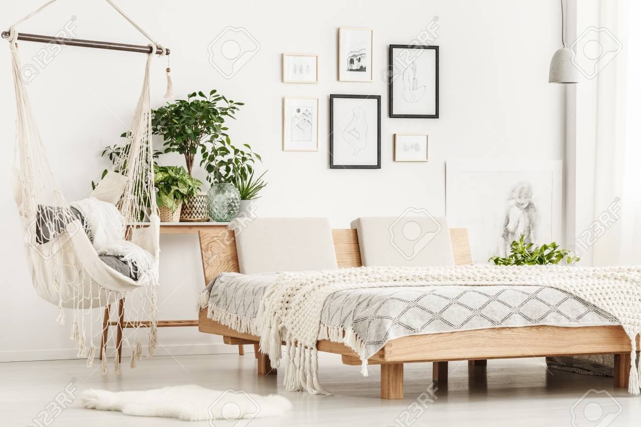 White Fur Rug Next To Wooden King Size Bed With Beige Blanket