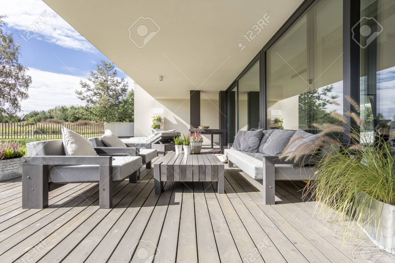 Neat and tidy terrace with wooden garden furniture and plants on table stock photo 97044613