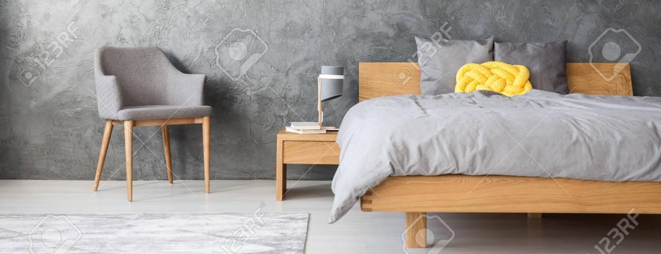 Gelbes Knotenkissen Auf Hölzernem Bett Im Grauen Schlafzimmer Mit ...