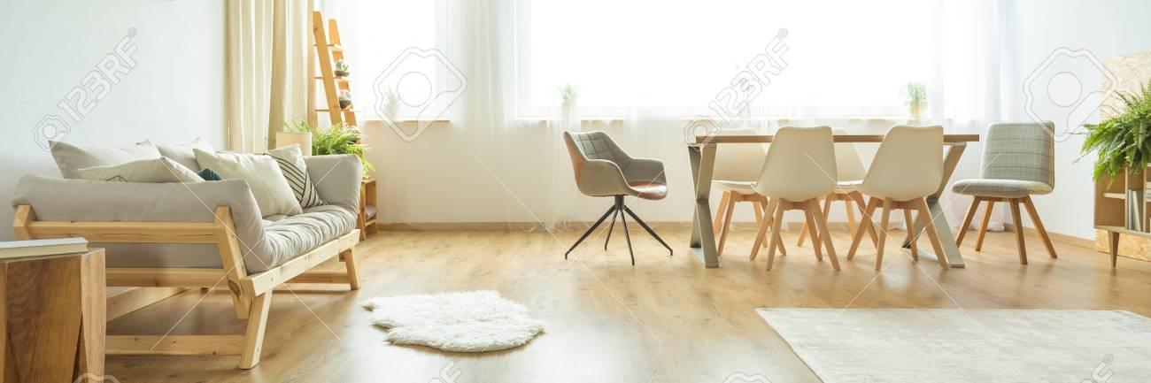Alfombra blanca en el piso de madera al lado de un sofá beige en el  luminoso comedor con sillas blancas y grises en la mesa