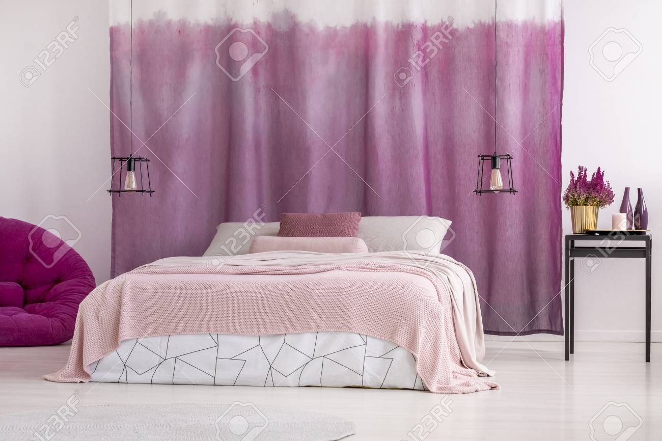 Flowers on black table near king-size bed with pink bedding against..