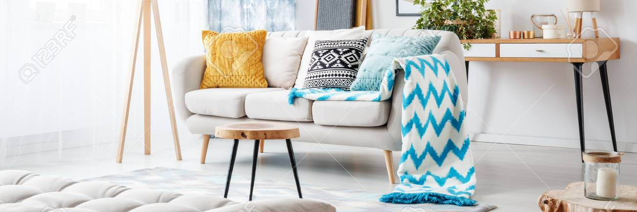 Close Up Of Blue Patterned Blanket On Sofa With Gold Pillow In Living Room  With