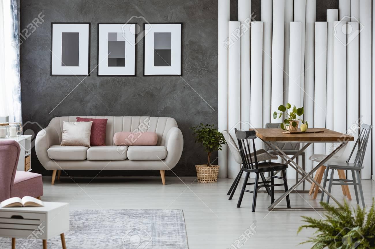 Buchen Sie Auf Weißen Schrank Im Gemütlichen Wohnzimmer Mit Kissen Auf Beige  Sofa Neben Esstisch Mit