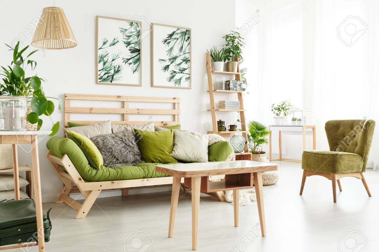 Wooden Table Near Green Armchair And Sofa In Natural Living Room ...
