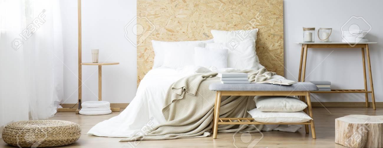 Hocker Und Holz In Warmem Naturlichem Schlafzimmer Mit Weissen Kissen