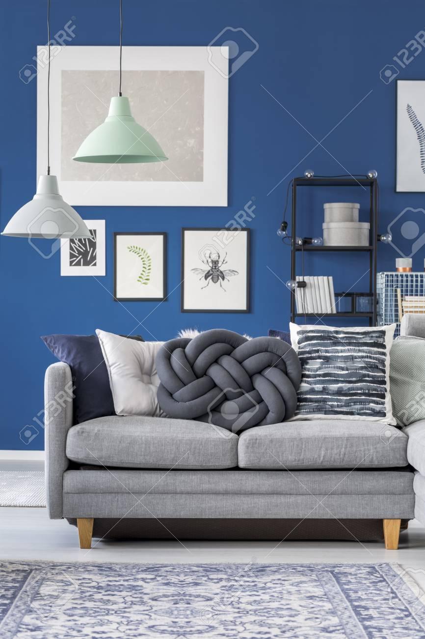 Close-up de canapé gris avec oreiller assis dans un salon bleu avec un  tapis de tapis