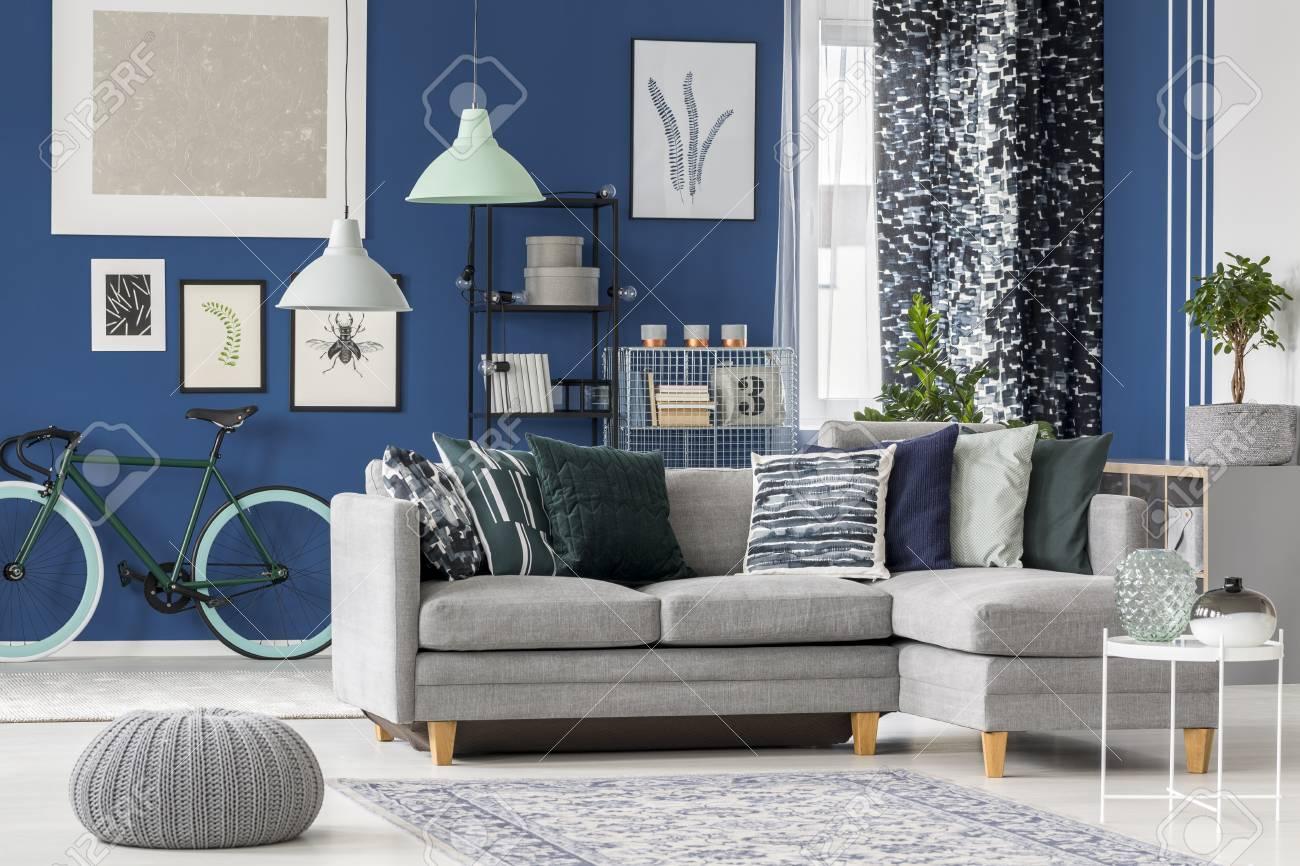 Salon bleu marine avec canapé d\'angle gris, coussins décoratifs et galerie  d\'affiches