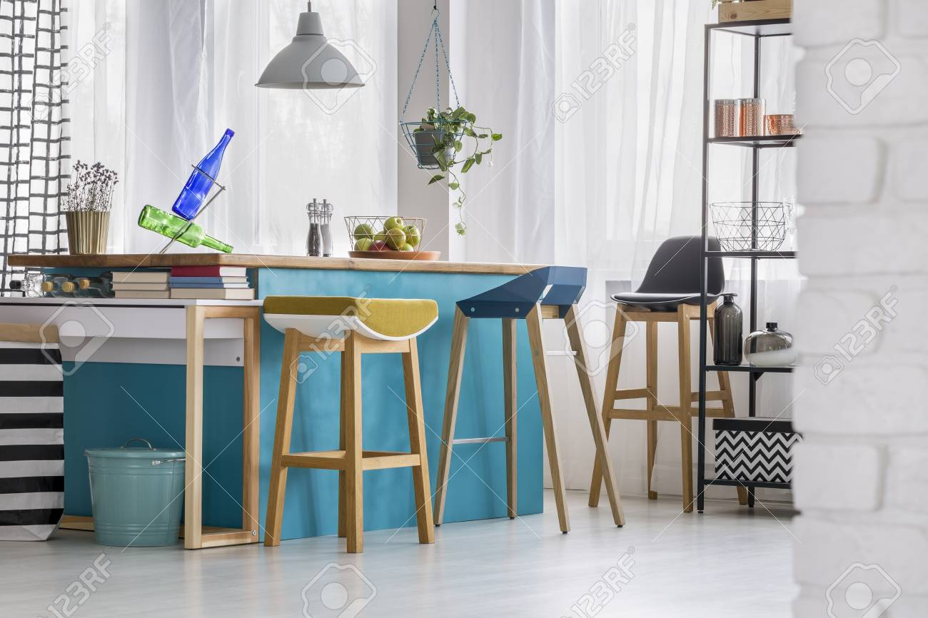 Picture of: Designer Bar Stools At Blue Kitchen Island With Bottles Under Stock Photo Picture And Royalty Free Image Image 93297317
