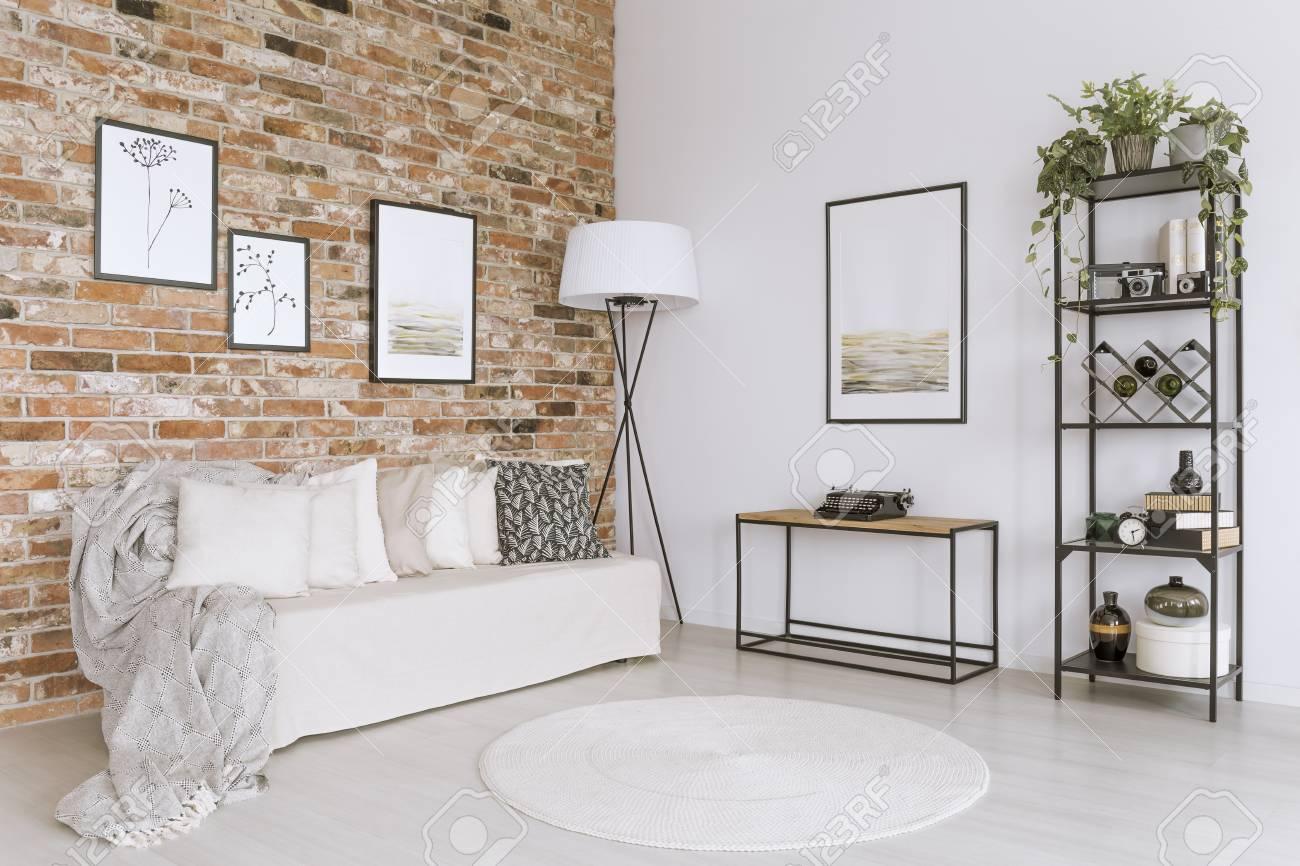 Canapé blanc avec des oreillers et tapis blanc dans le salon avec lampe sur  le mur de brique rouge avec galerie