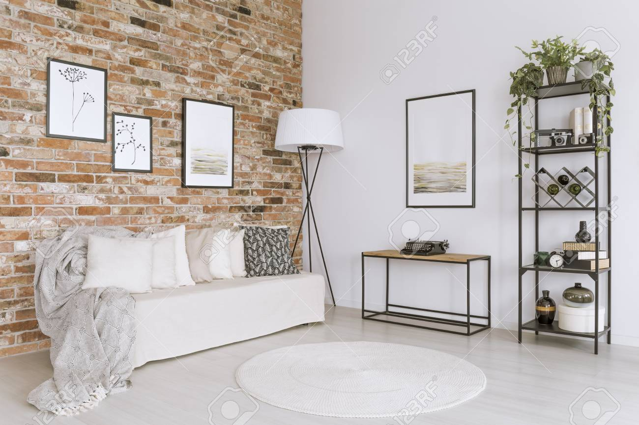 White sofa with pillows and white carpet in living room with..