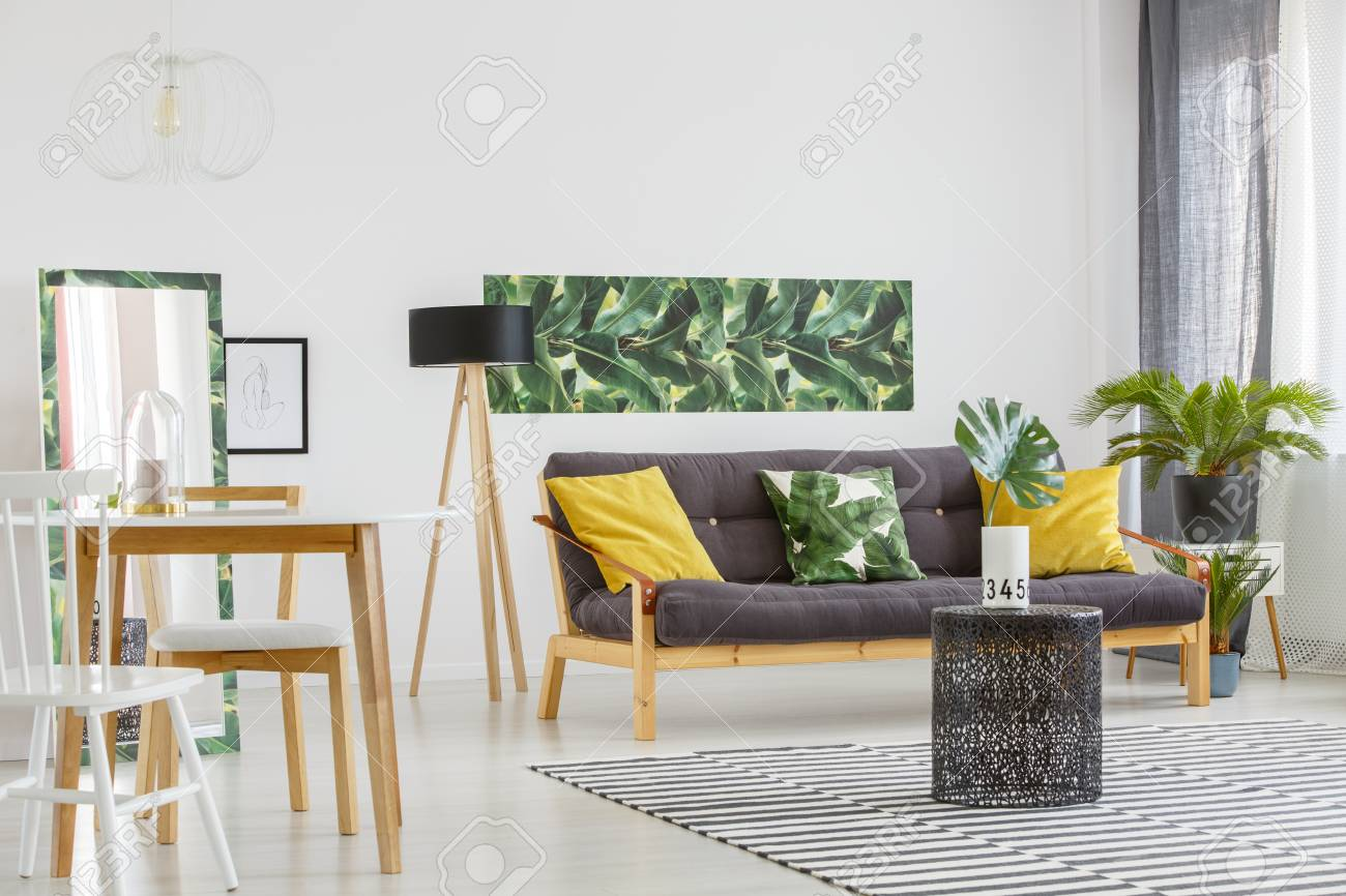 Gelbe kissen auf schwarzem sofa nahe lampe und stühlen am tisch im